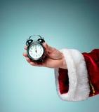 拿着一个老闹钟的圣诞老人 库存图片