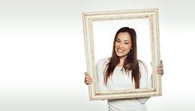 拿着一个老画框的微笑的妇女 免版税库存图片