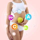 拿着一个苹果和桃子用他的手的妇女在腹部附近 免版税库存照片