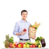 拿着一个苹果和袋子与食品的微笑的人 免版税库存图片