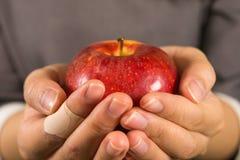 拿着一个苹果用两只手的一个女孩 免版税库存图片