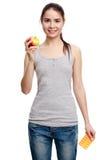 拿着一个药片和在t的年轻微笑的妇女在一只手上一个苹果 库存照片