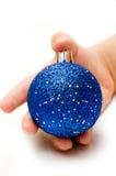 拿着一个蓝色圣诞节球的手 库存照片