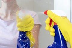 拿着一个蓝色清洗的浪花瓶的黄色橡胶手套的无法认出的妇女和洒玻璃镜子表面上 洗涤物 库存图片