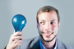 拿着一个蓝色电灯泡的英俊的年轻聪明的人 库存图片