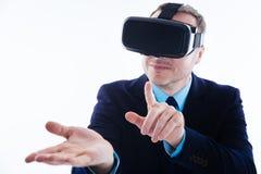 拿着一个虚拟设备的正面精明的商人 免版税库存照片