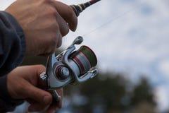 拿着一个转动的卷轴的渔夫手 图库摄影