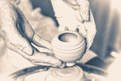 拿着一个逗人喜爱的小的黏土花瓶的主要陶瓷工 图库摄影