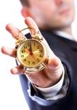 拿着一个金黄时钟的商人 免版税库存照片