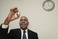 拿着一个金黄鸡蛋的人 库存图片