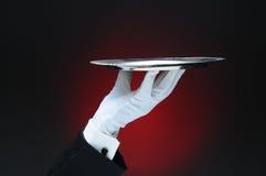 拿着一个银色服务盘子的侍者在他的指尖 免版税库存照片