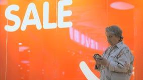 拿着一个银色电话的老年长妇女户内 股票录像