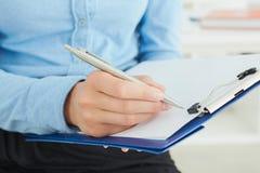 拿着一个银色笔特写镜头的女性手 做笔记的女商人在办公室工作场所 免版税库存图片