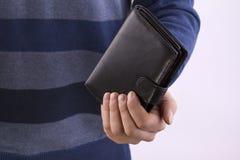 拿着一个闭合的钱包的人 免版税库存照片
