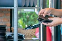 拿着一个黑色的盘子和碗架的手 免版税库存照片