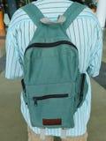 拿着一个经典绿色织品背包的年轻人 免版税库存照片