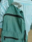 拿着一个经典绿色织品背包的年轻人 免版税图库摄影