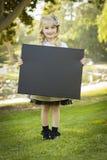 拿着一个黑黑板的逗人喜爱的矮小的白肤金发的女孩户外 图库摄影