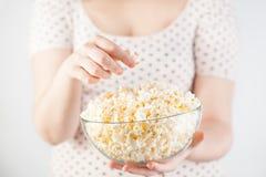 拿着一个玻璃碗玉米花的女孩 免版税图库摄影