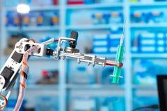 拿着一个医疗注射器的机器人 免版税库存图片