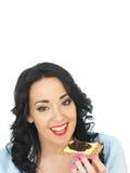 拿着一个整粒薄脆饼干用乳酪和腌汁的年轻愉快的妇女 库存图片