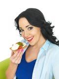 拿着一个整粒薄脆饼干用无盐干酪乳酪和新鲜的成熟蕃茄的年轻健康妇女 图库摄影