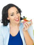 拿着一个整粒薄脆饼干用无盐干酪乳酪和蕃茄的年轻健康妇女 免版税库存照片