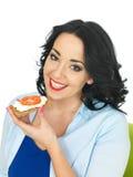 拿着一个整粒薄脆饼干用酸奶干酪和成熟新鲜的蕃茄的年轻健康妇女 库存照片