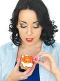 拿着一个整粒薄脆饼干用酸奶干酪和新鲜的成熟蕃茄的年轻健康妇女 库存照片
