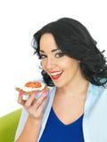 拿着一个整粒薄脆饼干用酸奶干酪和新鲜的成熟蕃茄的年轻健康妇女 免版税库存照片
