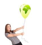 拿着一个绿色地球气球的愉快的夫人 免版税库存图片