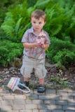拿着一个紫色复活节彩蛋的男孩 图库摄影