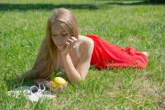 拿着一个黄色苹果和读一本书的女孩在夏天公园 图库摄影