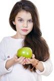 拿着一个绿色苹果的一个美丽的小女孩的画象 库存照片