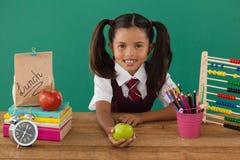 拿着一个绿色苹果的女小学生反对绿色背景 库存图片