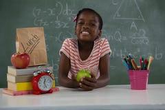 拿着一个绿色苹果的女小学生反对绿色背景 库存照片