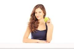 拿着一个绿色苹果的美丽的女性 库存照片