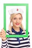 拿着一个绿色画框的年轻女性水手 免版税库存照片