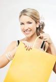 拿着一个黄色购物袋的一名年轻白肤金发的妇女 免版税库存照片
