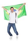 拿着一个巴西标志的一个愉快的人的纵向 库存照片