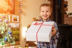 拿着一件礼物的愉快的男孩新年 库存图片