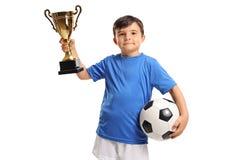 拿着一件金黄战利品的小足球运动员 库存照片