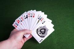 拿着一副牌在绿色的男性手感觉背景 免版税图库摄影