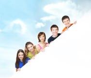 拿着一副白色横幅的一个小组年轻少年 库存图片