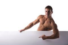 拿着一副白色横幅的坚强的肌肉赤裸上身的年轻人 库存图片