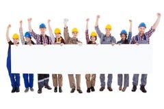 拿着一副空白的白色横幅的小组工作员 免版税库存照片