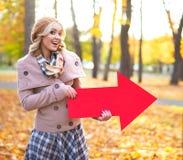 拿着一副箭头横幅的可爱的女孩在公园 库存照片