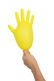 拿着一副膨胀的黄色手套的女性手 免版税图库摄影