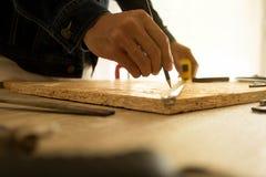 拿着一卷措施磁带的男性木匠特写镜头在车间 免版税库存图片