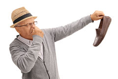 拿着一双有臭味的鞋子的老人 免版税库存图片